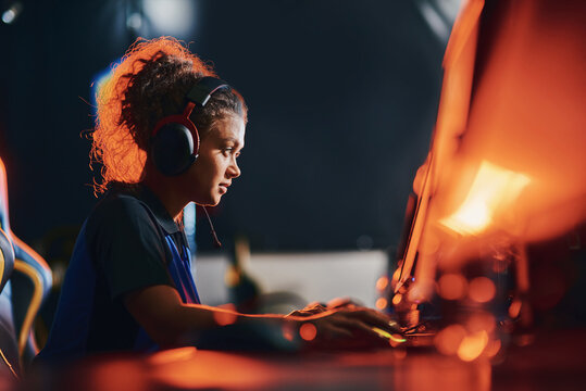 Side view of a young mixed race girl, female cybersport gamer wearing headphones playing online video games, participating in eSport tournament