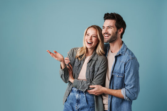Young beautiful excited man and woman hugging and pointing finger