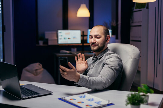 Entrepreneur waving during online call on smartphone with someone. Businessman in the course of an important video conference while doing overtime at the office.