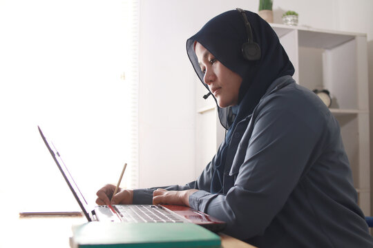 Asian muslim woman having video teleconference on her laptop at home, online learning or working from home