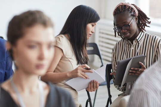 Portrait of two young women talking while sitting in audience at business conference or seminar, copy space