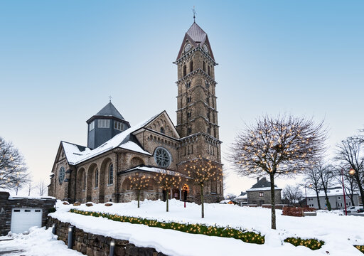 Beautiful church in Butgenbach surrounded by a winter landscape with illuminated Christmas lights in the trees around Christmas time.