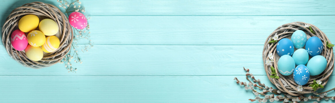 Flat lay composition with colorful Easter eggs on light blue wooden table, space for text. Horizontal banner design