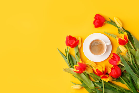 Coffee mug with bouquet of red yellow tulips and copy space for notes good morning on bright yellow table, beautiful breakfast, vintage card, top view, flat lay, 8 march woman day, mother day, romance