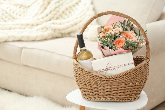 Wicker basket with gifts on table indoors. Space for text
