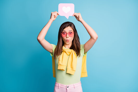 Photo of pretty person hold heart paper above head pink sunglass tied on shoulders sweater isolated on blue color background