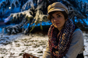 Photo of a young and attractive woman with short hair sitting on a bench surrounded by snow wearing winter clothes and smiling at the camera. Blue sky during the night. Magical landscape Wall mural