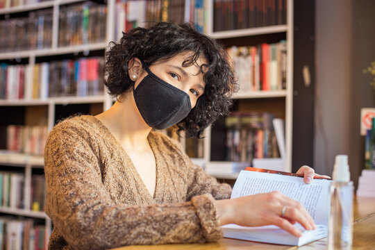 Woman with anti virus mask in library reading book.