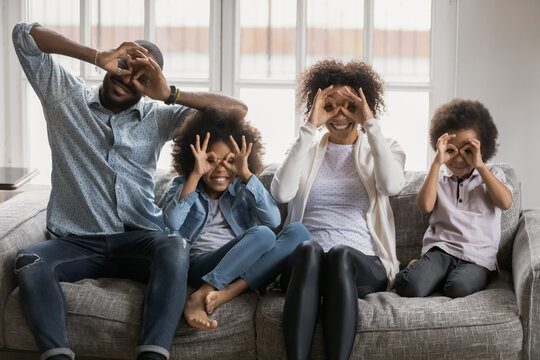 Portrait happy African American parents and kids making funny faces, sitting on couch at home, smiling mother and father with laughing little siblings showing binoculars glasses eyewear shape gesture