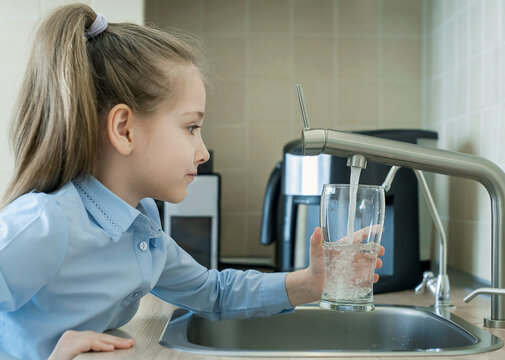 Child is holding a transparent glass. Filling cup beverage. Pouring fresh drink. Consumption of tap water contributes to the saving of water in plastic bottles and to the protection of the environment