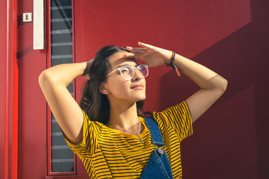 Portrait of a beautiful caucasian teenager girl wearing glasses and colorful clothes with her right hand behind her head and left hand over her eyes. Dark red door on the background. Copy space.