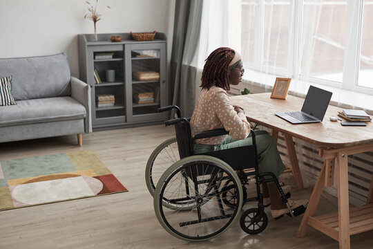 Full length portrait of African-American woman in wheelchair calling by video chat while sitting at desk with laptop in minimal grey interior, copy space