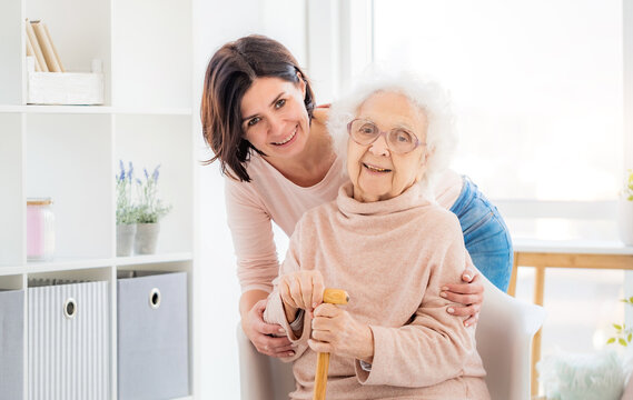 Happy elderly woman embraced by daughter at home