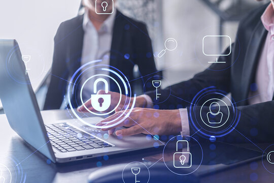 Two businesspeople in formal wear working on the project to protect cyber security of international company using laptop. Padlock Hologram icons. Teamwork concept.