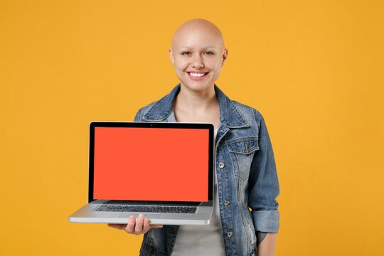 Young bald caucasian friendly happy woman 20s without hair in casual denim jacket white t-shirt hold laptop pc computer with blank screen workspace area isolated on yellow background studio portrait