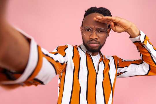 Serious assertive african man blogger with dreadlocks, in striped shirt looking far away with hand over head, looking for new subscribers, posing selfie. Indoor studio shot isolated on pink background