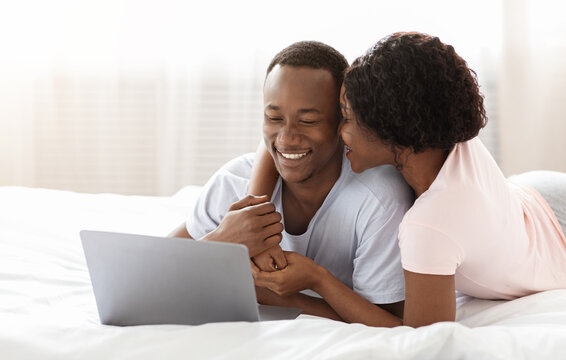 Romantic black man and woman using laptop in bed