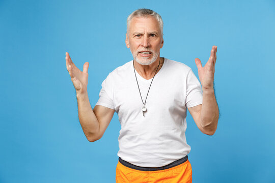 Elderly gray-haired sportsman indignant angry trainer instructor coach man 50s in sportswear white t-shirt whistle spreading hands isolated on blue background studio portrait. Fitness sport concept