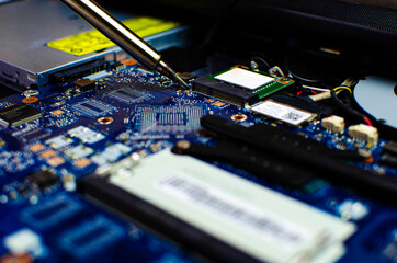 Man use blue color soldering iron to fix mainboard or motherboard chipset close up shot with other fixing tools concern engineer workshop and industrial in 2021 Wall mural