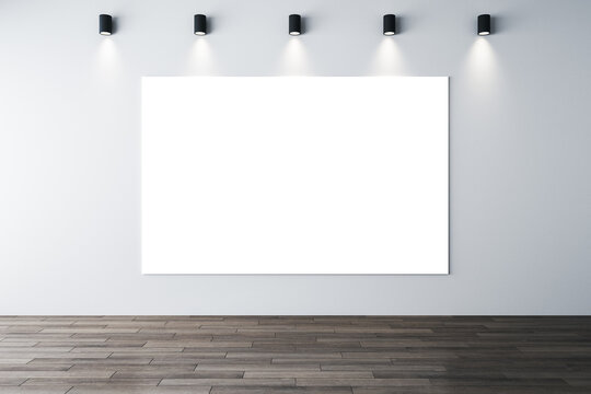 Minimalistic interior with lamps on ceiling and poster on wall.