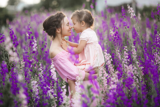 Young beautiful mother and her little daughter outdoors with flowers. Violet field of flowers and people there