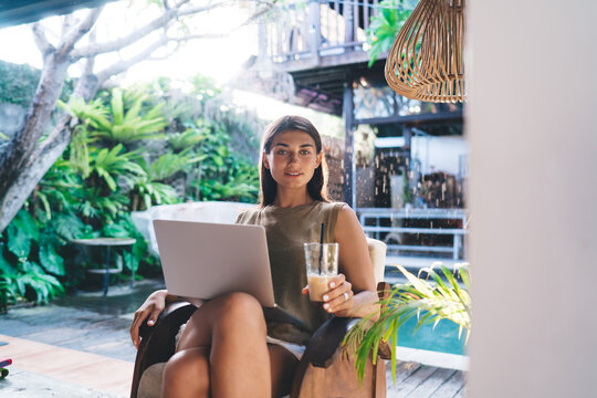 Successful lady with beverage surfing laptop during break