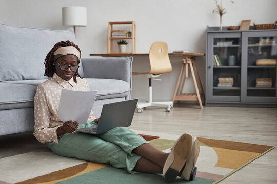 Full length portrait of modern African-American woman working from home while sitting on floor on graphic carpet and using laptop, copy space