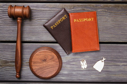 Honeymoon trip concept. Wooden gavel with two passports and wedding costumes flat lay.