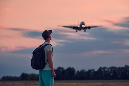 Young man looking up at flying airplane against moody sky during dusk. Themes nostalgia for travel and aviation.
