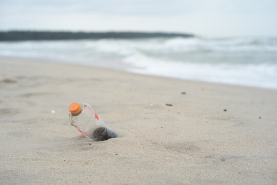 Selective focus on the plastic bottle on the beach with blurred seascape in background. Trash and garbage