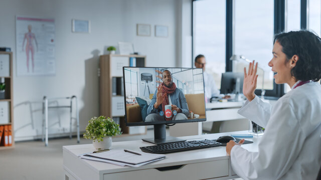 Female Medical Doctor is Making a Video Call with Sick Patient on a Personal Computer in a Health Clinic. Assistant in Lab Coat is Talking About Health Issues in Hospital Office.