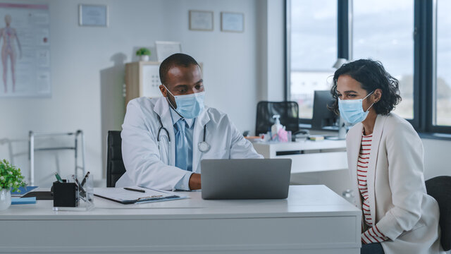 Family Doctor in Protective Mask is Reading Medical History of Female Patient and Speaking with Her During Consultation in a Health Clinic. Physician in Lab in Front of Computer in Hospital Office.