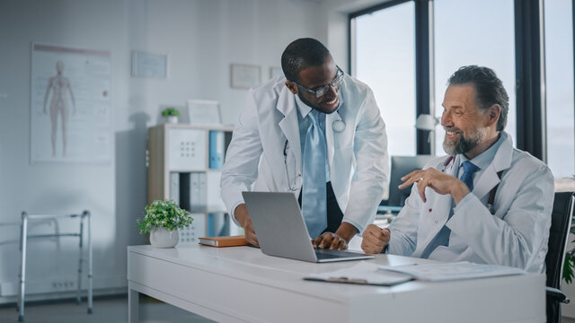 Young African American Physician is Talking to a Senior Doctor in a Medical Health Clinic. Colleagues Discuss Work on Laptop Computer in Hospital Office. Assistant Asks Medical Advice from a Doctor.