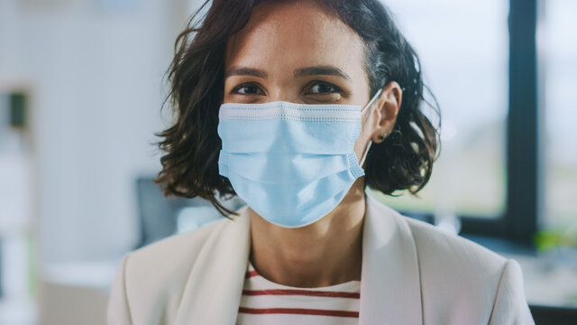 Portrait of Beautiful Latin American Female with Short Dark Curly Hair is Wearing a Protective Mask in a Hospital Room. Casually Dressed Woman Wearing Face Mask to Slow the Spread of Virus.