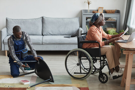 Full length portrait of African-American man assembling furniture in home interior with woman in wheelchair working at desk, handyman service and assistance concept, copy space