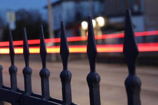 calle pasando coches y luces de los coches entre la reja en una sola direccion por obturación lenta.