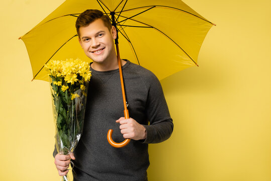 Smiling man with flowers and umbrella looking at camera on yellow background
