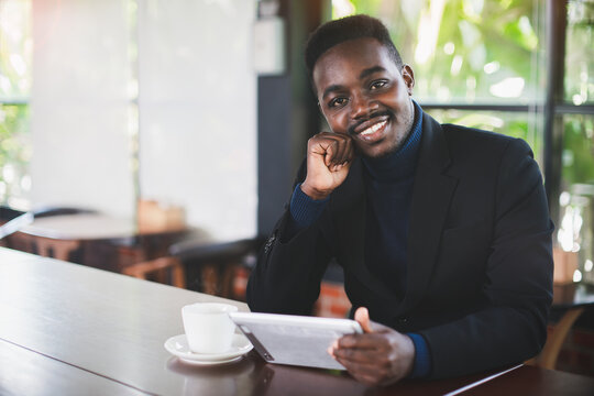 African businessman using tablet computer in restaurant