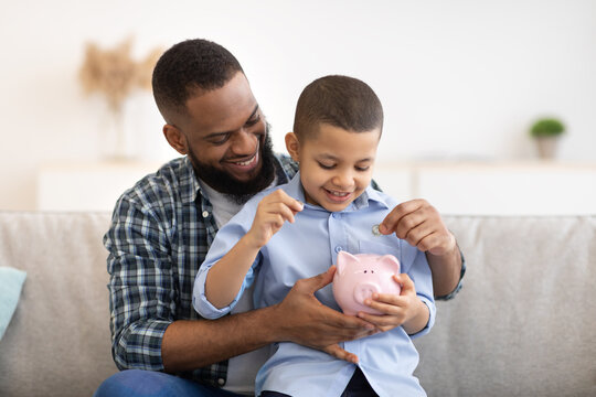 African Father And Son Putting Money In Piggybank At Home