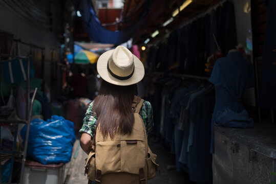 Asian female tourist traveling and shopping stall at outdoor local street market in Bangkok Thailand on vacations