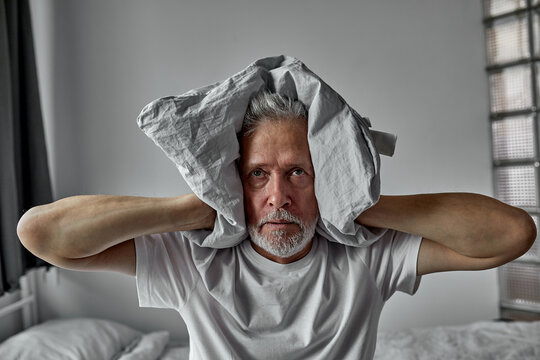 elderly man is tired of hearing voices, schizophrenia, closes ears with blanket, at home alone
