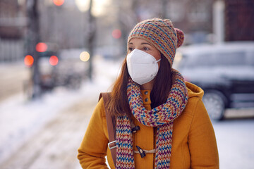 Middle-aged brunette woman in winter clothes wearing face mask outdoors due to Corona virus outdoors while on her way to work
