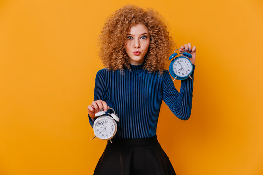 Blue-eyed curly blonde lady in striped sweater and skirt whistles and poses with alarm clocks on yellow background