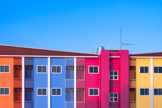Glass windows and safety baluster with stainless steel water tank on high section of colorful apartment building against blue sky background