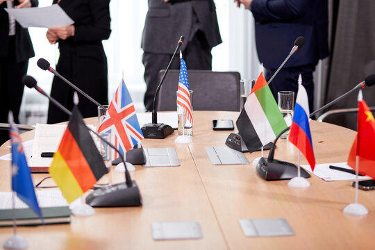 close-up photo of table and small flags on it, no people sitting at desk in the office, after meeting