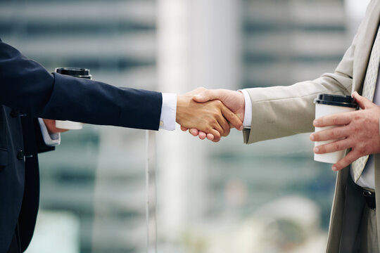 Close-up image of business people with take out coffee shaking hands when greeting each other before meeting