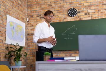Caucasian male maths teacher standing by blackboard giving online lesson using laptop