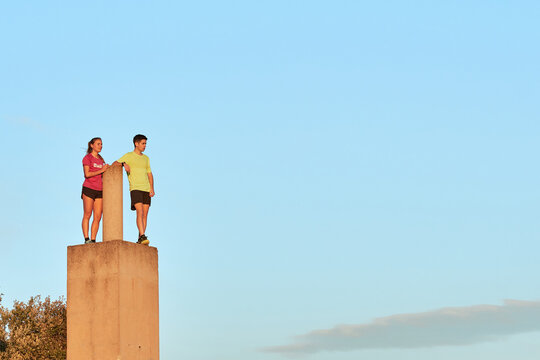 Low angle of sportsman and sportswoman standing near stone pillar on background of blue sky at sundown and relaxing during training