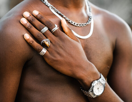 Unrecognizable crop African American male with naked torso showing hand with trendy silver rings