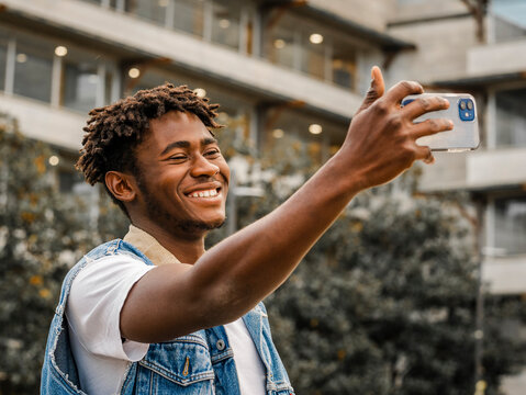 Side view of cheerful young bearded African American hipster guy with dreadlocks taking selfie on mobile phone for sharing with friends in social network while standing against urban building on street